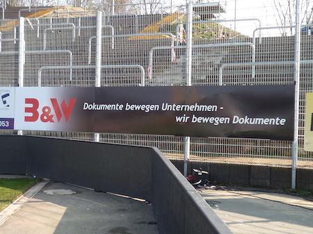 Banden- und Stadionwerbung Beispiel Stadionwerbung an einem Zaun.